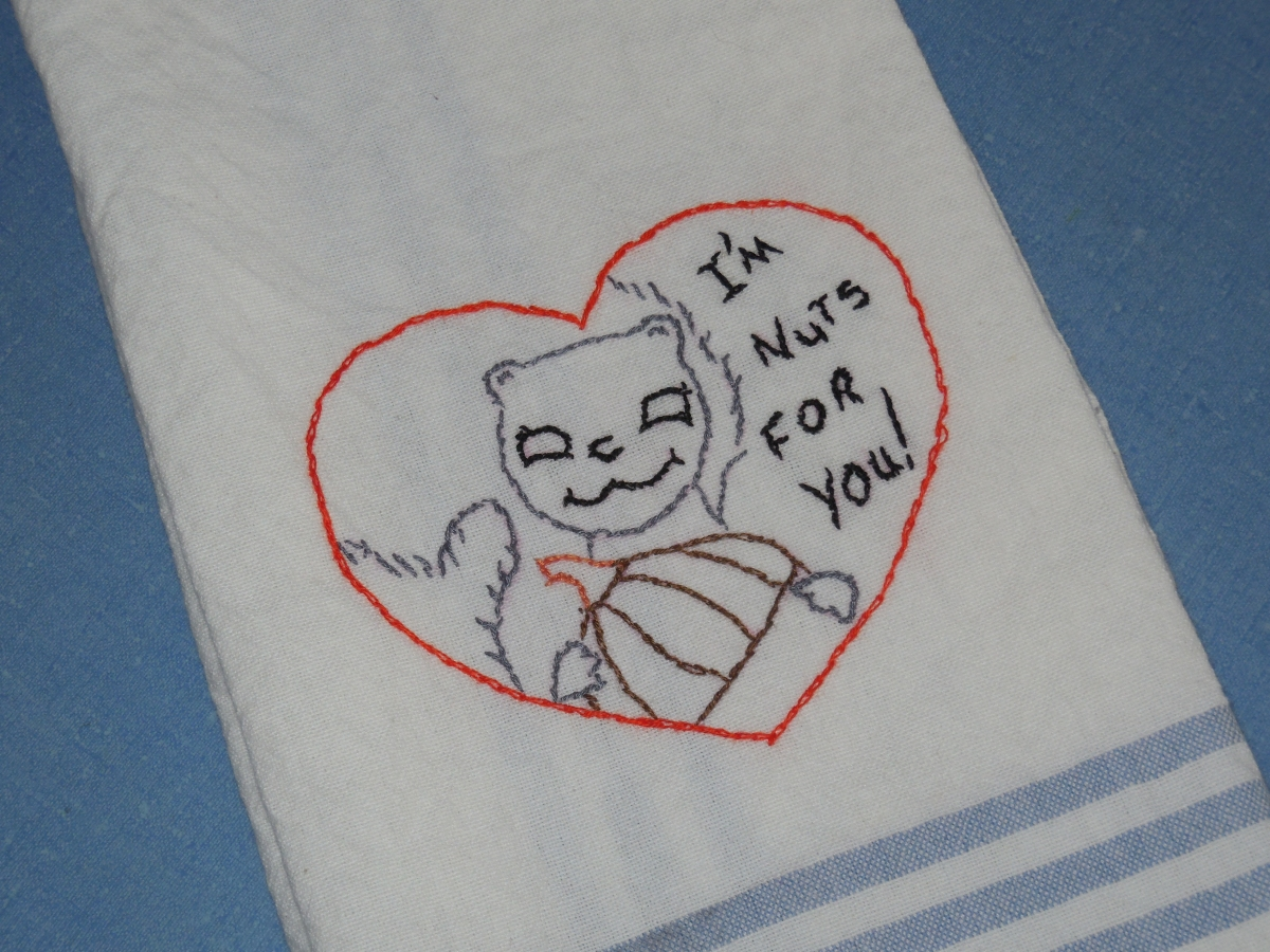 "photograph of embroidered hand towel. The embroidery is of a heart and within the heart is a squirel, holding a nut with the words ""I'm nuts for you!"""